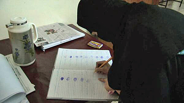 Woman signing into Hina Jilani center