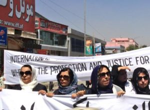 Afghan Women Hold Banner/Photo: Bethany Matta for USA Today