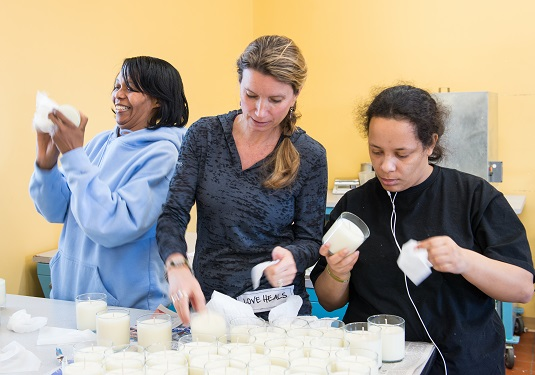 Becca Stevens working with employees at the candle and body products business, Thistle Farms--with Ty left and Jordan right--Photo: Peggy nappier