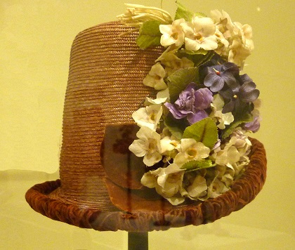Tall Hat, 1884: Plaited Straw, silk velvet, cotton plain weave, metallic thread, artificial flowers at Legion of Honor, SF/Photo: Courtesy Wendy Verlaine