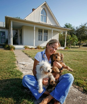 Beth Howard i nfront of her Gothic House rental, Iowa/Photo Courtesy Beth Howard